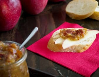 red paper napkin with baguette slice on top with 3 apple slices and a dollop of onion jam with bacon in it; 2 slices baguette in background, 2 red apples in back left corner and jar of onion jam in front corner with small spoon in it