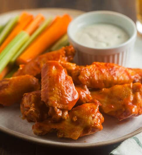 buffalo wings on white plate with carrot and celery sticks and dip in small white bowl