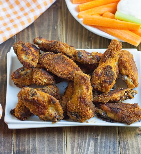 breaded cooked chicken wings on a white rectangle platter with an orange gingham cloth in the background and a plate with carrot and celery sticks
