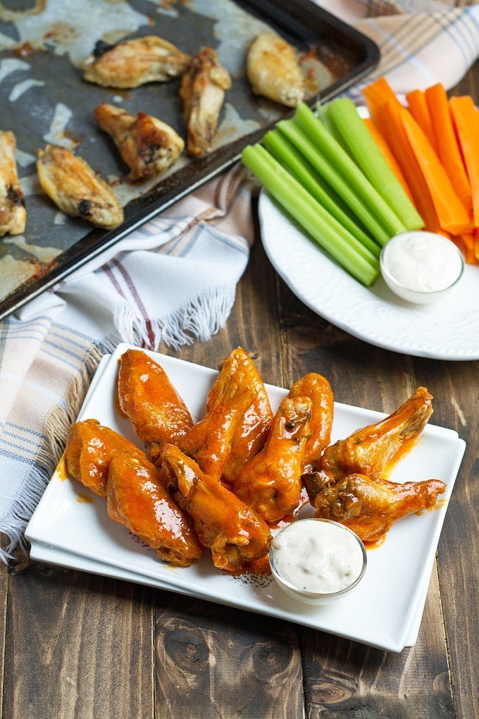 buffalo wings on rectangular white platter with blue cheese dressing in small bowl; white cloth with blue striping in back left; celery and carrots on plat in back right