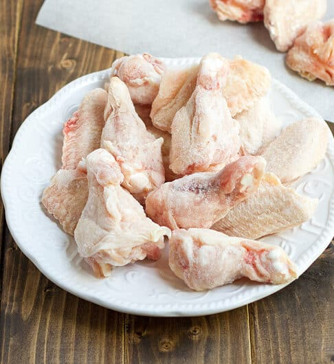 frozen chicken on white plate with cutting board in background