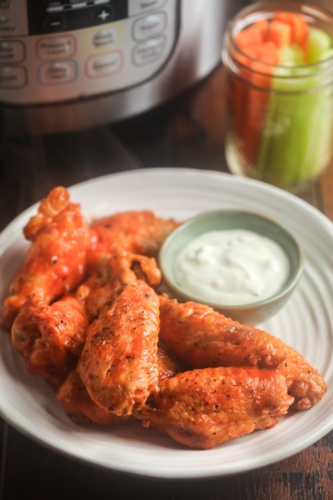 Buffalo wings on a white plate with blue cheese dressing; jar with carrot and celery stick in jar in background and instant pot