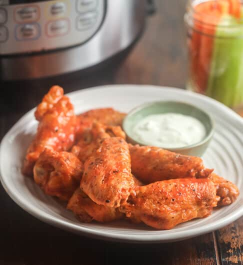 buffalo wings on a white plate with a condiment dish of blue cheese dip, instant pot and jar of carrot and celery sticks in background