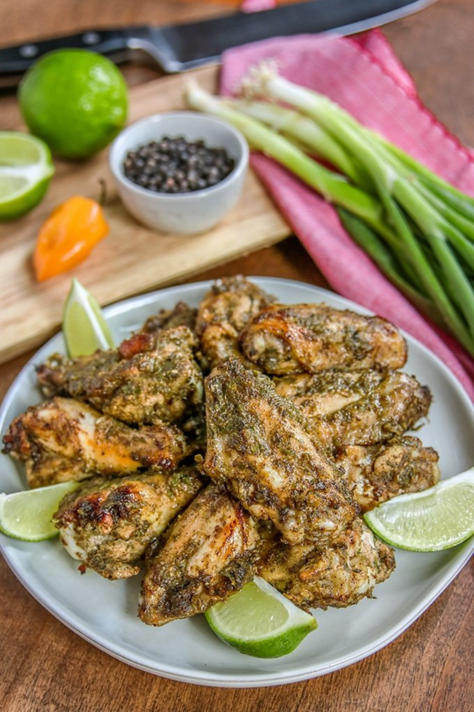 well seasoned chicken wings on light gray plate garnished with lime wedges; light pink cloth in background with bunch of green onions; cutting board with condiment bowl with seasonings, orange habanero pepper, and lime