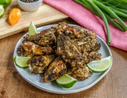 well seasoned chicken wings on light gray plate garnished with lime wedges; light pink cloth in background with bunch of green onions; cutting board with condiment bowl with seasonings, orangehabanero pepper, and lime
