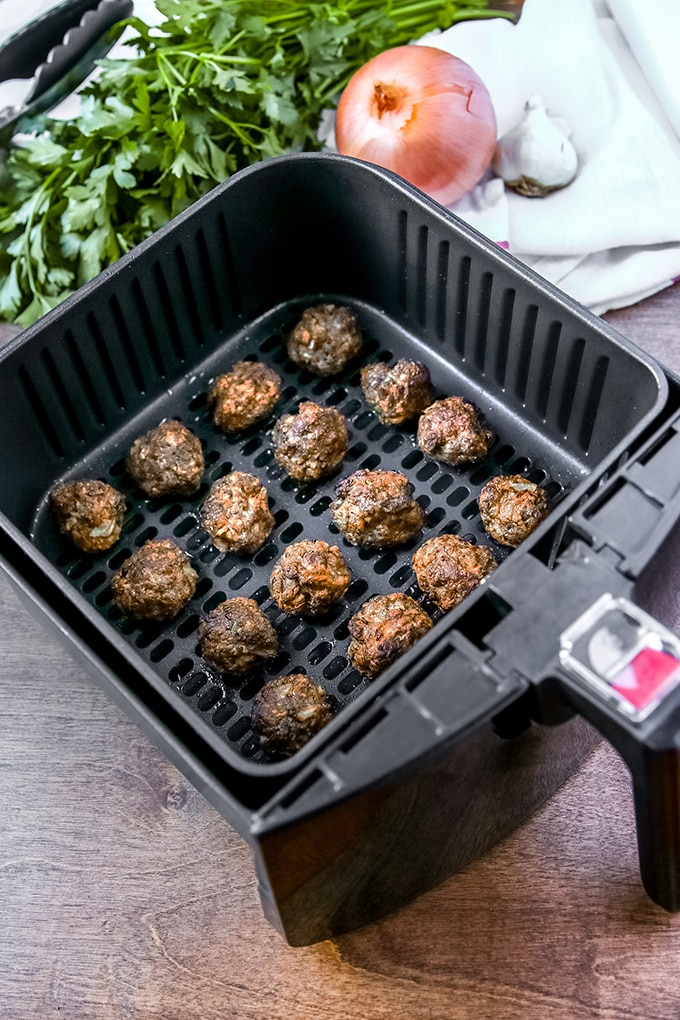 meatballs in air fryer basket with herbs in background