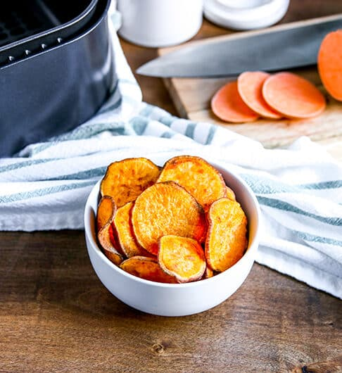 white bowl with sweet potato chips; white and blue striped cloth behind it; cutting board with sliced sweet potato and knife on it; air fryer basket to back left