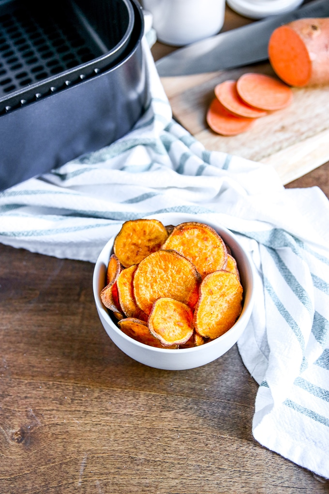 white bowl with sweet potato chips; white and blue striped cloth behind the bowl. Cutting board in background with sliced sweet potato; air fryer basket in back left corner