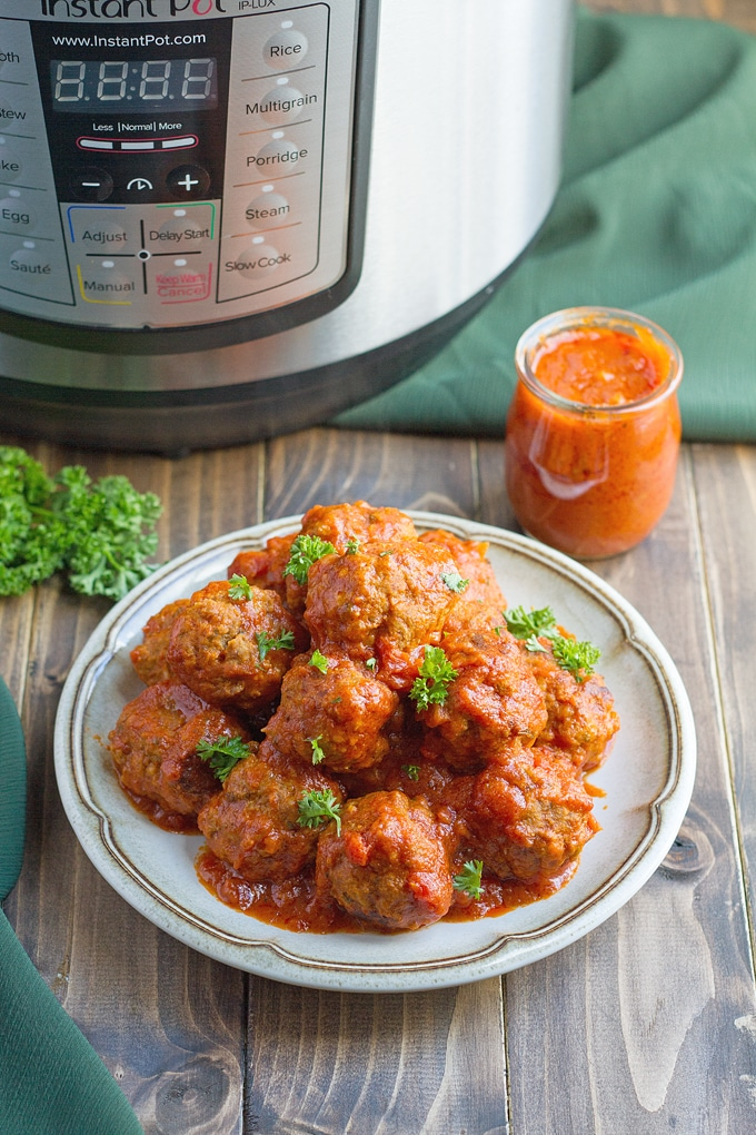 meatballs in sauce on white plate with herb garnish; small jar of sauce in background with green herbs to side and instant pot in background with green cloth on table in background