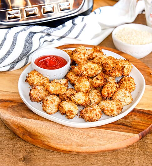 breaded chicken bites on white plate on top wooden server; small white bowl ketchup on plate; white condiment bowl and glass measuring cup to back right, and white cloth with black stripe to back left; bottom of air fryer in top corner