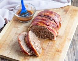 bacon wrapped meatloaf with 2 slices on wooden cutting board; bbq sauce in condiment jar with basting brush in background