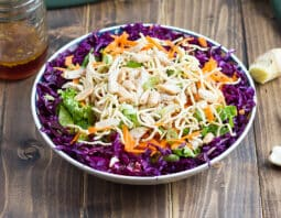 bowl with purple cabbage, lettuce, chicken, peanuts, carrots, crunchy rice noodles; garlic, ginger, and dressing in a jar in background