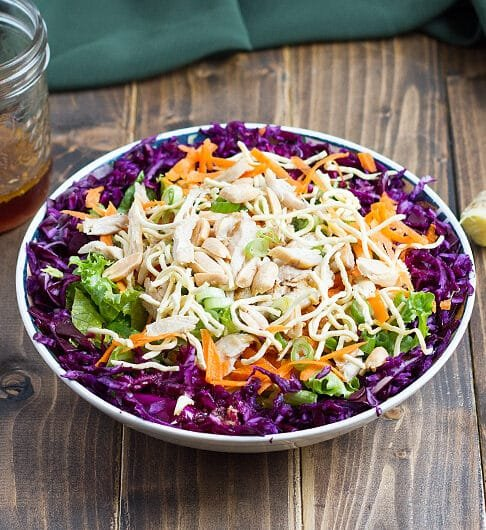 bowl with purple cabbage, lettuce, chicken, peanuts, carrots, crunchy rice noodles; garlic, ginger, and dressing in a jar in background; green cloth in background