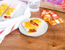 2 grilled cheese burrito on white plates with taco bell plater and sauce packets in background