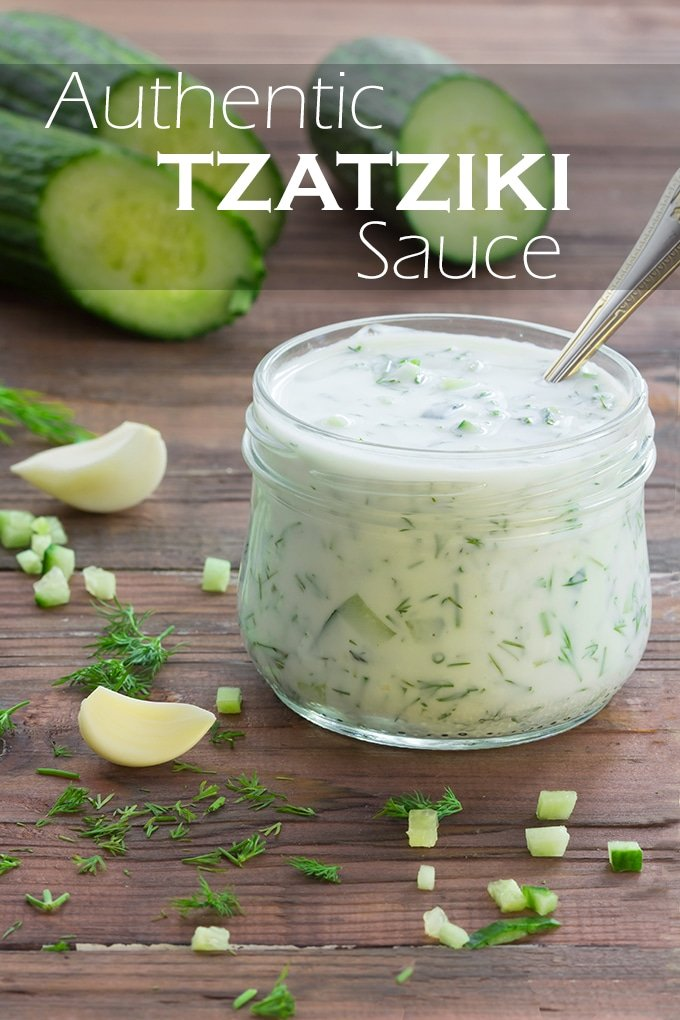 Tzatziki sauce in a short jar with garlic cloves, chopped cucumber, and dill scattered around, cucumbers in the background. The words Authentic Tzatziki Sauce appear on the image.