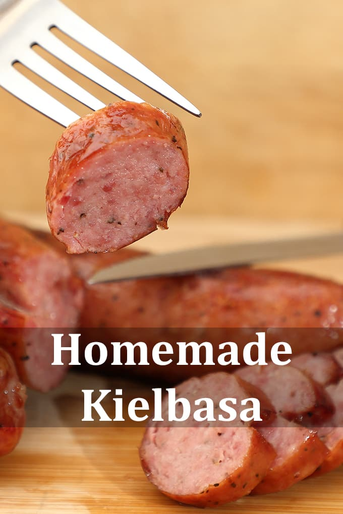 """Slices of kielbasa on a wooden surface. One slice is held up on a fork. The words """"Homemade Kielbasa"""" are on the image."""