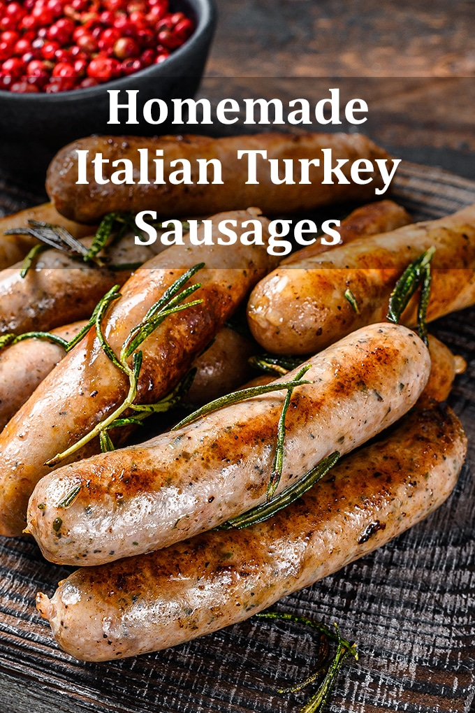 """Cooked turkey sausage links on a wooden table with herbs scattered over top and a bowl of berries in the background. The words """"Homemade Italian Turkey Sausages"""" appear on the image."""