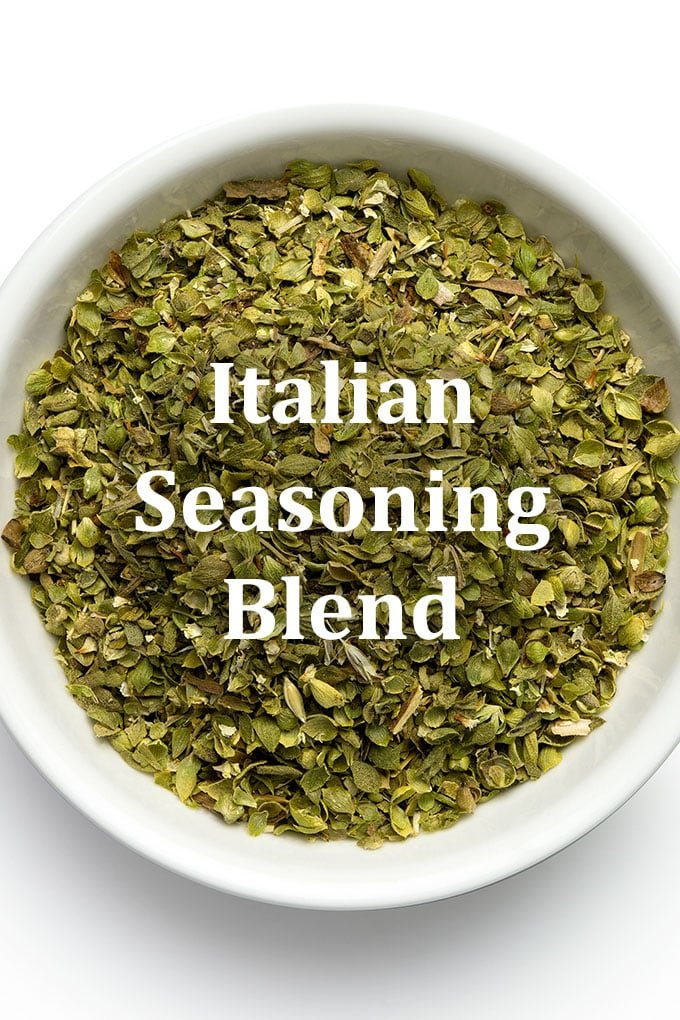 A white bowl with a mixture of green dried herbs, with the words Italian Seasoning Blend overlayed on the image.