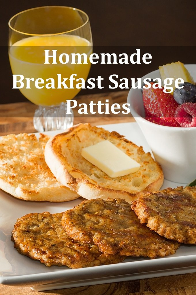 """Three breakfast sausage patties cooked and overlapping on a plate. An English muffin with butter is behind it as is a bowl of berries and a glass of juice. The words """"Homemade Breakfast Sausage Patties"""" appear on the image."""