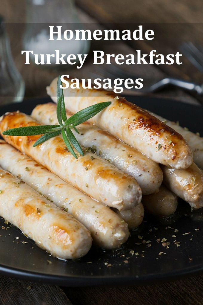 """Turkey breakfast sausages in a pile on a black plate. The words """"Homemade Turkey Breakfast Sausages"""" are on the image."""