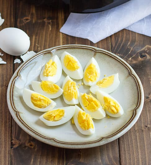 tan plate with brown line around edge with quartered hard boiled eggs on plate; white cloth in background as well as whole hard boiled egg with broken shell