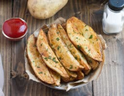 potato wedges garnished with parsley on paper lined dish with condiment bowl of ketchup behind it, salt shaker, and whole potato; gray cloth to side