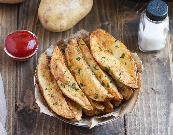 potato wedges garnished with parsley on paper lined dish with condiment bowl of ketchup behind it, salt shaker, and whole potato