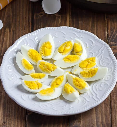 white plate with quartered hard boiled eggs on it; with shells in background and orange striped cloth