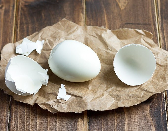 hard boiled egg on brown paper with shell in several large pieces