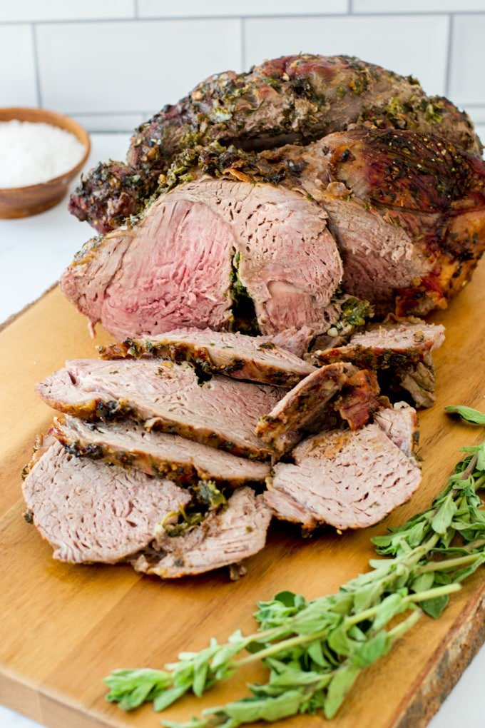 boneless leg of lamb, half of it sliced; a bit of pink in the middle; fresh green herbs in front of roast; small condiment bowl in background with salt in it