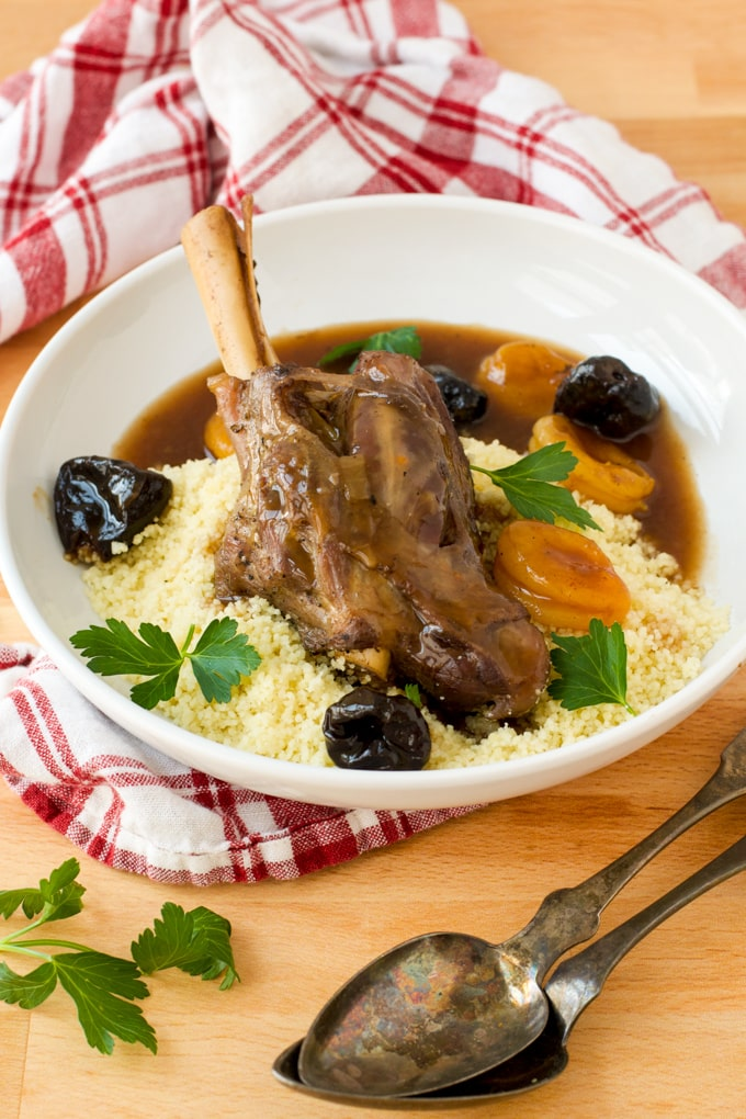 lamb shank served in white bowl over couscous with fresh herb garnish, figs, apricots, and au jus; red and white checked cloth under bowl, serving spoons in front of bowl,