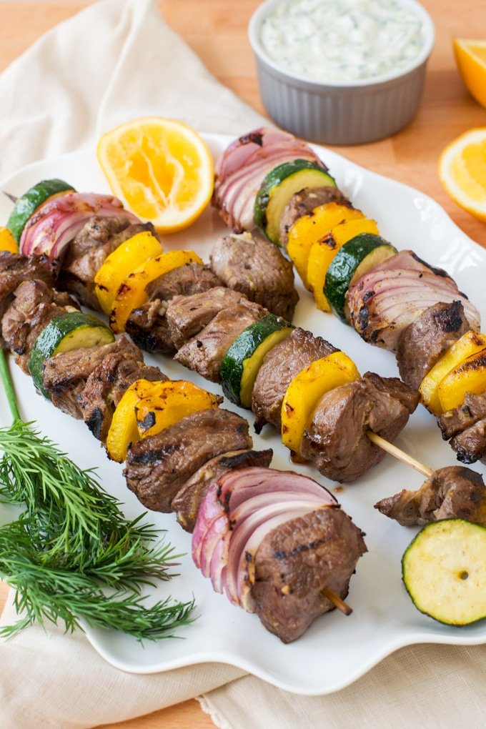 skewers with lamb, red onion, zucchini, and yellow bell pepper on them; lemon and tzatziki sauce in background