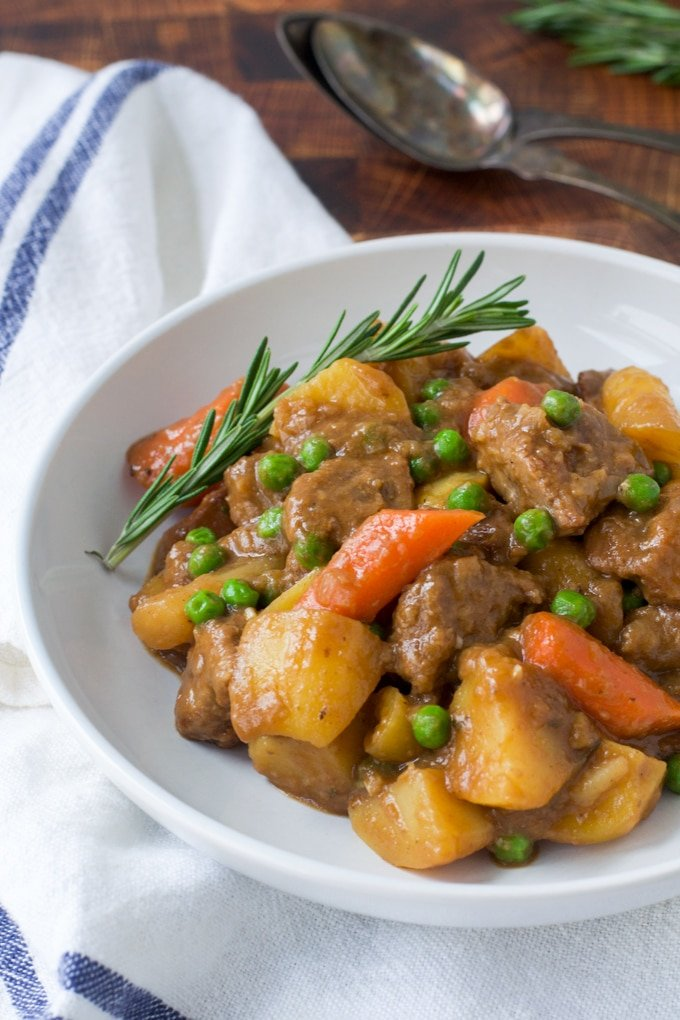 lamb, potato, carrots, peas in a white bowl with sprig of rosemary