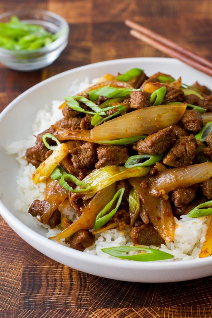 lamb stir fry over rice with sliced scallion garnish