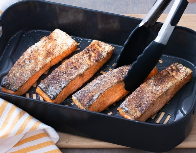 salmon filets in air fryer basket with tongs holding one piece; yellow and white striped cloth under basket