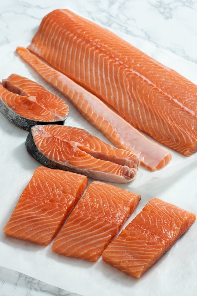 side of salmon, salmon filets, and salmon steaks on paper towel