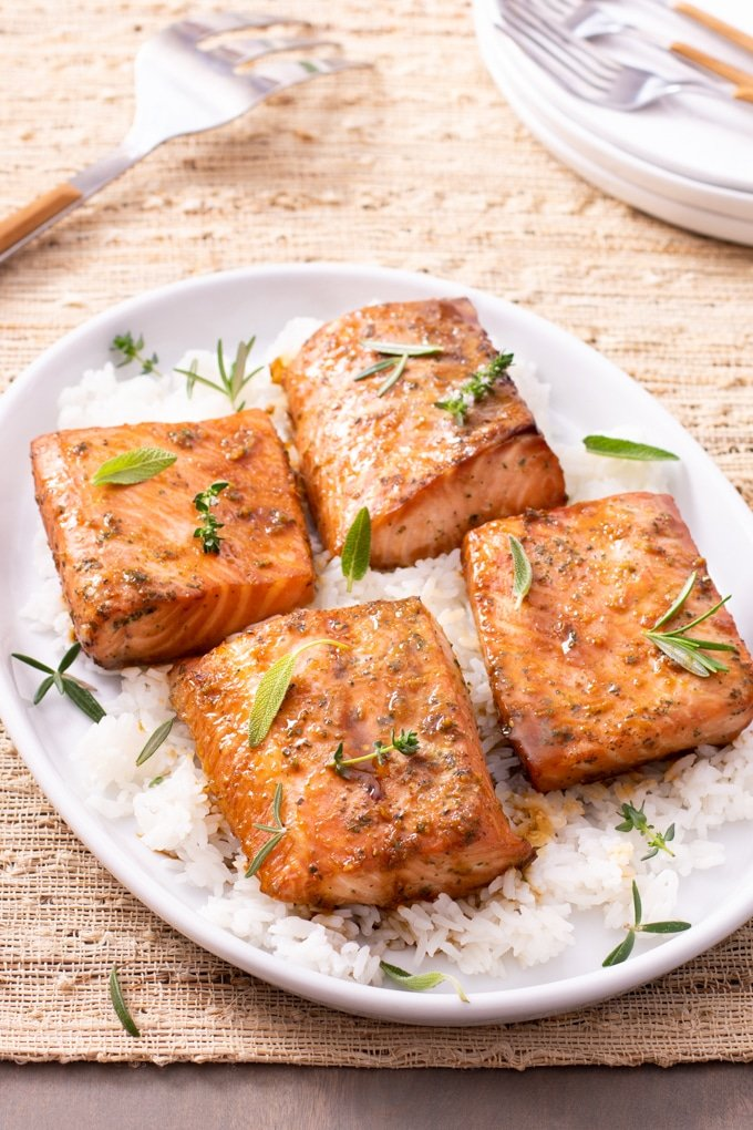 cooked salmon on top of bed of rice garnished with fresh herbs; stack of plates and forks showing in top right corner