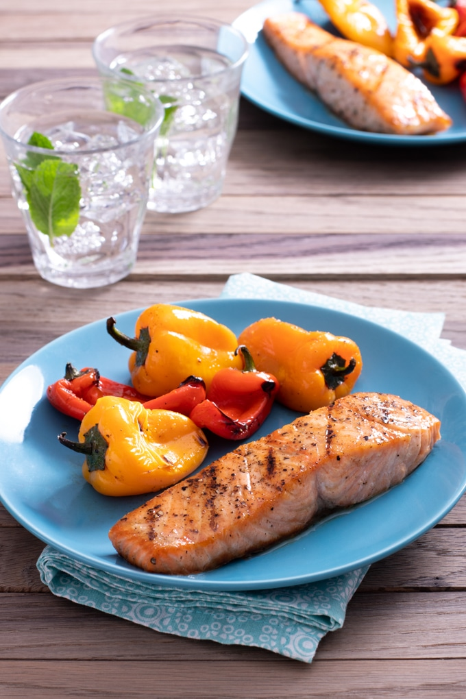grilled seasoned salmon on light blue plate with grilled baby bell peppers; blue napkin under plate; glasses of water in background as well as second plate of same food