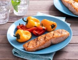 grilled seasoned salmon on light blue plate with grilled baby bell peppers; blue napkin under plate; glasses of water in background