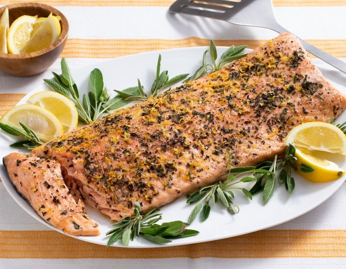 salmon crusted with sage, lemon zest and black pepper with sage and lemon wedge garnish on white platter with yellow an dwhite striped cloth under plate; small bowl of lemon wedges in background