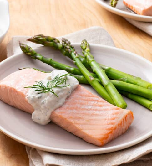 white plate topped with salmon fillet, topped with a lemon dill sauce and dill garnish; asparagus on plate; condiment dish with lemon dill sauce in background