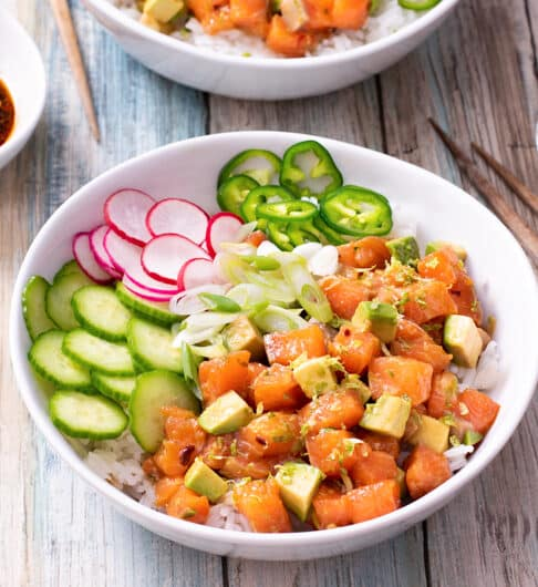 white bowl with cubed salmon, avocado, sliced cucumber, radished, and jalapenos on rice; chopsticks to right, small dish of sliced cucumber and radish in right hand corner; sliced green onion and soy sauce in condiment bowls to left