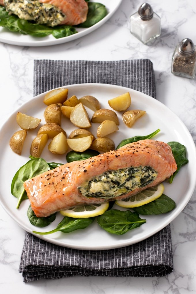 salmon topped with seasoning and stuffed with spinach and cream cheese laying on a bed of spinach and lemon slices; on a white plate with quartered and roasted small potatoes forks to left of plate, salt and pepper to right, second plate of food in top left corner