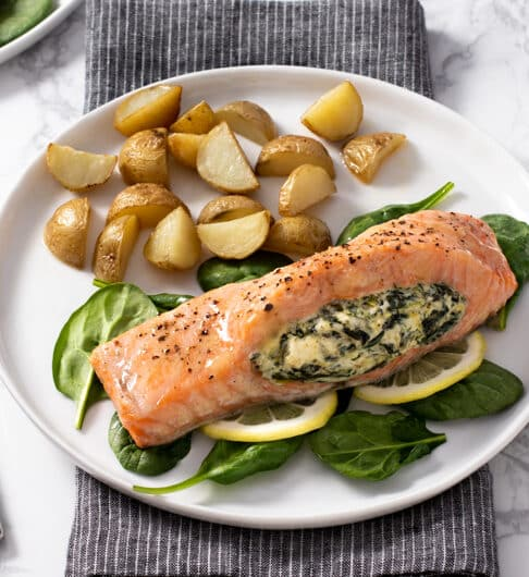 salmon topped with seasoning and stuffed with spinach and cream cheese laying on a bed of spinach and lemon slices; on a white plate with quartered and roasted small potatoes forks to left of plate, salt and pepper to right