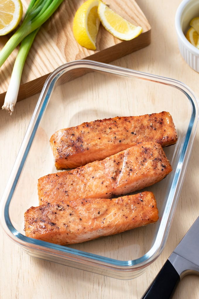baked salmon filets in glass container with green onion and lemon wedges in background