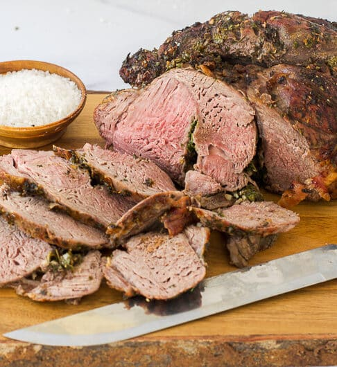 boneless leg of lamb, half sliced with knife in front of it and fresh green herbs to left; small condiment bowl of salt behind it