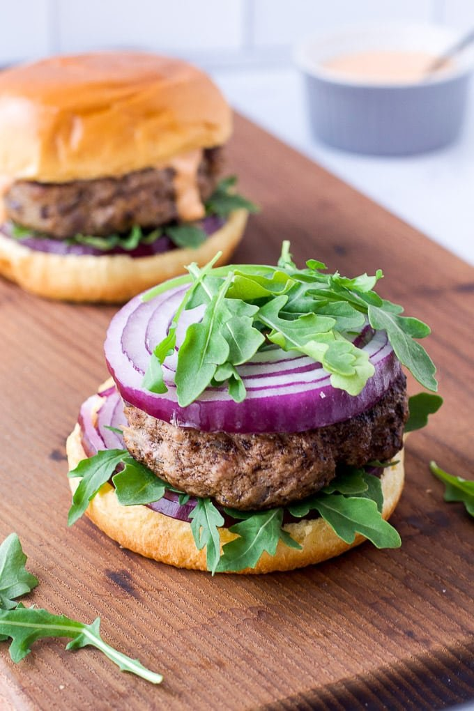 lamb burger on bun with arugula and red onion with another burger in background