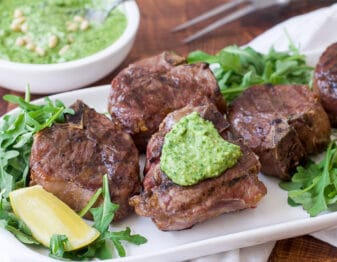 grilled lamb chops on bed of arugula on white platter garnished with green pesto and lemon wedges; condiment bowl of green pesto behind it