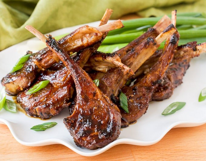 fried lamb lollipops on white platter garnished with slivers of green onion, light green cloth in background