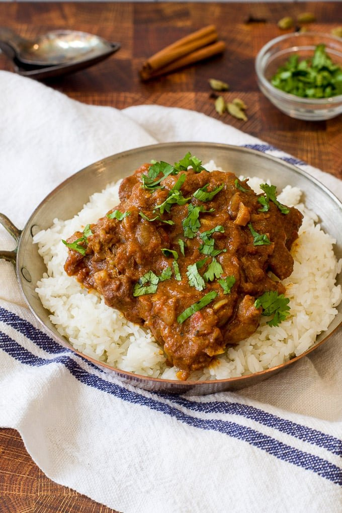bowl with rice topped with indian lamb stew with an herb garnish; white and blue striped cloth under bowl; cinnamon stick and fresh green herb in background
